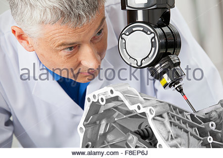 Close up of engineer using computer controlled probe to scan engine block - Stock Photo