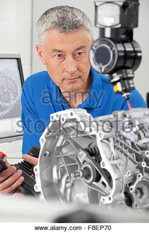 Engineer with joystick controlling probe scanning engine block - Stock Photo