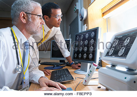 Surgeon and radiologist viewing digital brain scan in hospital - Stock Photo