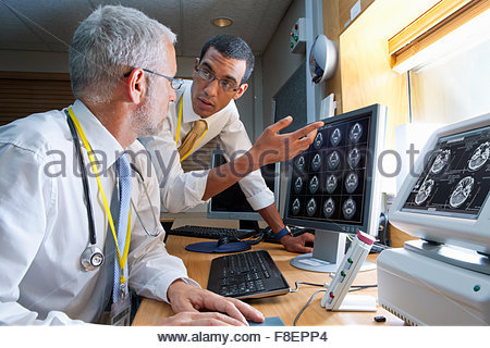 Surgeon and radiologist discussing digital brain scan in hospital - Stock Photo