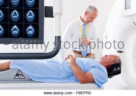 Doctor and patient at CT scanner behind digital brain scan in hospital - Stock Photo