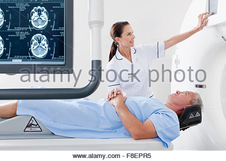 Technician nurse and patient at CT scanner behind digital brain scan in hospital - Stock Photo