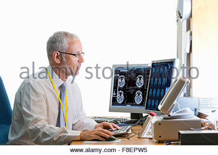 Doctor reviewing digital brain scan in doctor - Stock Photo