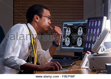 Focused doctor reviewing digital brain scan in doctor - Stock Photo