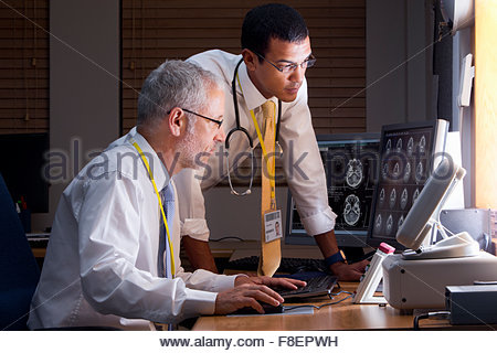 Serious doctors reviewing digital brain scan in doctor - Stock Photo