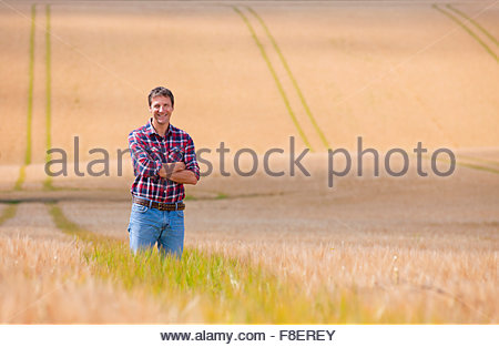 Portrait confident farmer standing in sunny rural barley crop field in summer - Stock Photo