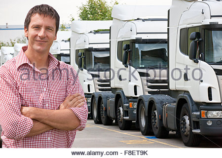 Portrait of confident freight transportation truck driver owner near trucks parked in a row - Stock Photo