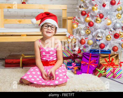 Girl in the red hat and the funny round glasses sits on a rug in the room with New Years interior - Stock Photo