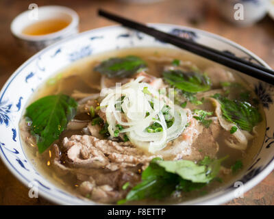 A bowl of beef brisket pho, a popular Vietnamese noodle soup. - Stock Photo