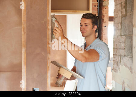 Plasterer Working On Wall On Building Site - Stock Photo