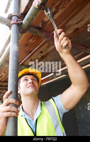 Builder Putting Up Scaffolding - Stock Photo