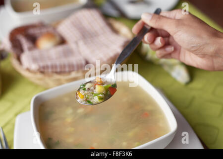 Young woman eating hot and healthy soup. - Stock Photo