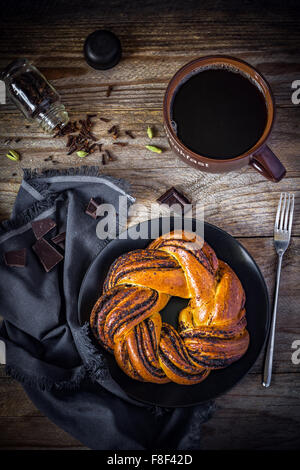 Sweet pastry and cup of black coffee on vintage wooden table, top view - Stock Photo