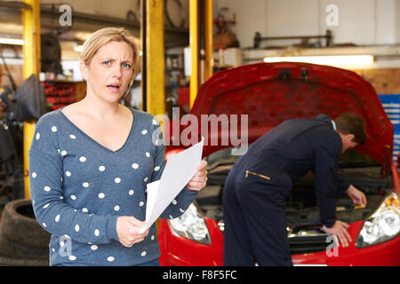 Shocked Customer Looking At Garage Bill - Stock Photo