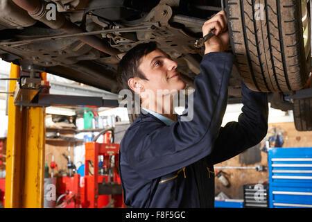 Trainee Mechanic Working Under Car - Stock Photo