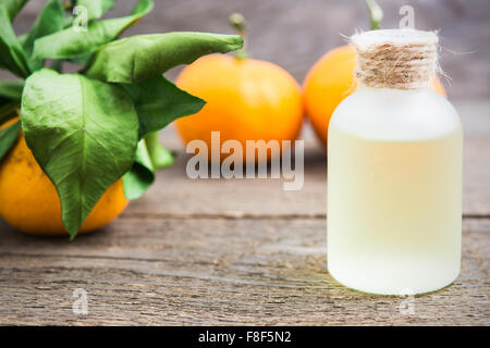 Tangerine oil in a glass bottle with fresh tangerines on wooden background - Stock Photo