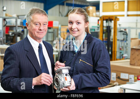 Factory Manager And Engineering Apprentice Discussing Component - Stock Photo