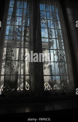 looking out through net curtains stock photo