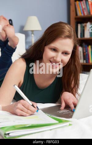 Teenage Girl Using Laptop To Do Homework In Bedroom - Stock Photo