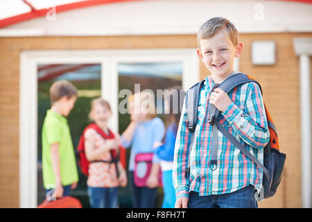 Boy Standing Outside School With Rucksack - Stock Photo