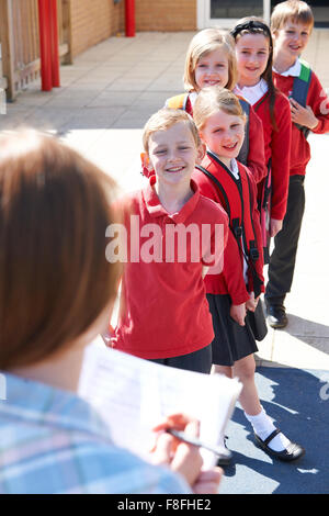 Teacher Taking School Register In Playground - Stock Photo