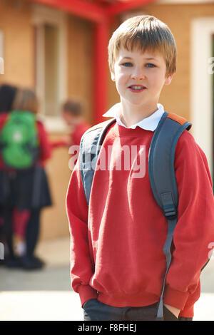 Boy Wearing Uniform Standing In School Playground - Stock Photo