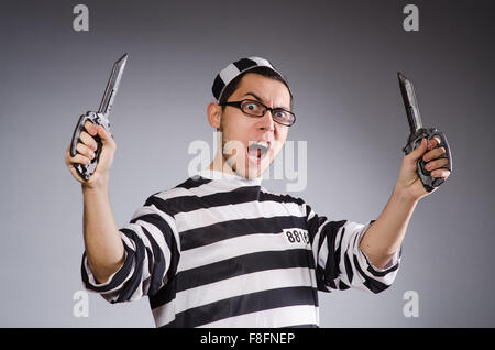 Funny prisoner with knuckles isolated on gray - Stock Photo