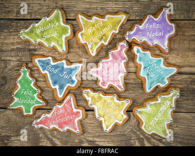 Christmas gingerbread cookies with seasonal greetings in ten international languages placed on wooden rustic boards - Stock Photo