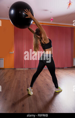 Full Length Rear View of Young Woman Wearing Exercise Clothing Standing in Dance Studio with Hardwood Floor and - Stock Photo
