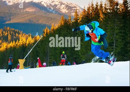 Snowboarder jumping in Bukovel ski resort. Bukovel is the most popular ski resort in Ukraine. - Stock Photo