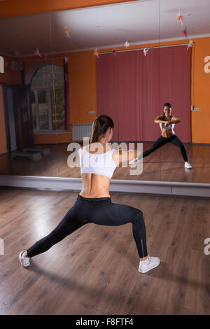Full Length Rear View of Young Brunette Woman Wearing Exercise Clothing and Stretching Arms and Legs in Dance Studio - Stock Photo