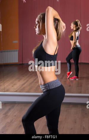 Three Quarter Length Side Profile View of Young Blond Woman Wearing Exercise Clothing Stretching Arms Behind Head - Stock Photo