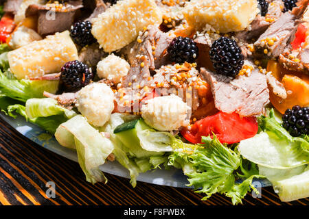 Close Up of Gourmet Salad Made with Fresh Fruit and Vegetables, Variety of Cheeses and Meats on Rustic Wooden Table - Stock Photo