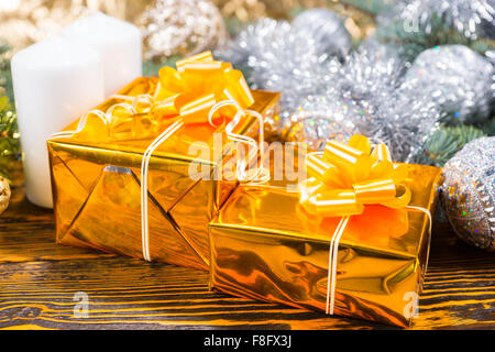 Christmas arrangement with two gift boxes wrapped in shiny golden paper, white candles and pine branch decorated - Stock Photo
