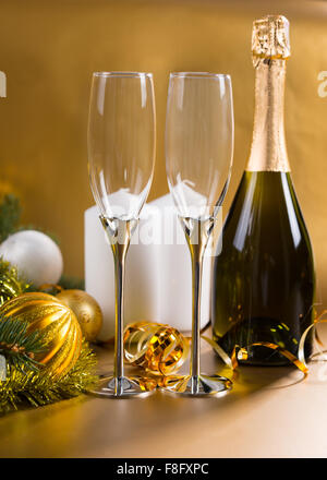 Festive Still Life of Two Elegant Glasses on Golden Background with Bottle of Champagne, White Pillar Candles, and - Stock Photo
