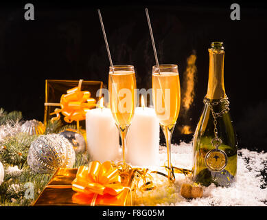 Festive Christmas still life with sparklers in flutes of romantic champagne, golden gifts, baubles and burning candles - Stock Photo