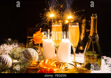 Celebrating Christmas and the New Year festive season with sparklers and champagne in a still life arrangement with - Stock Photo