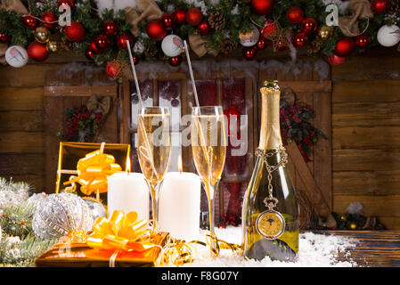 Festive Still Life - Bottle of Champagne with Two Full Glasses on Snow Covered Surface with Lit Candles and Gold - Stock Photo