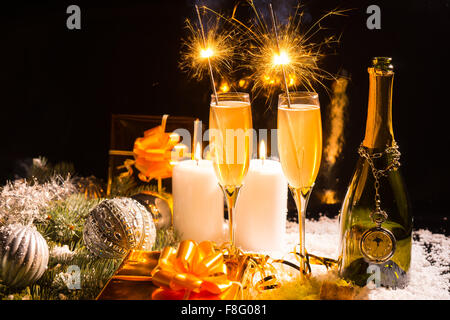 Festive Still Life - Celebratory Glasses of Champagne with Burning Sparklers on Snow Covered Surface with Lit Candles, - Stock Photo