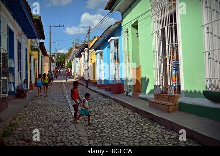 children playing on a cobbled street lined with colorful houses in Trinidad Sancti Spiritus Province Cuba - Stock Photo