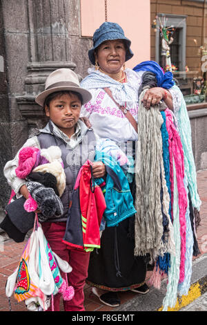 Woman selling hand made scarves and crafts on a street in Quito, Ecuador. - Stock Photo
