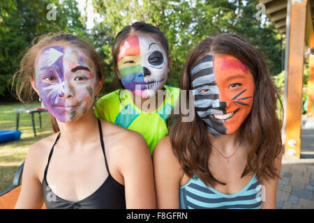 Smiling girls wearing face paint - Stock Photo