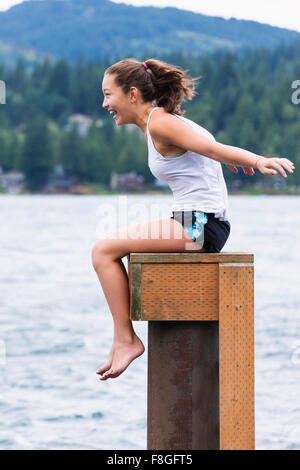 Mixed race girl sitting on wooden pedestal at lake - Stock Photo