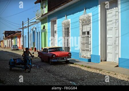 vintage motorbike and side car driving on cobbles past a parked red vintage car Trinidad Sancti Spiritus Province - Stock Photo