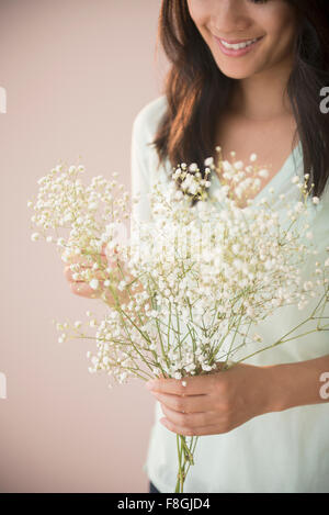 Chinese woman holding bunch of flowers - Stock Photo