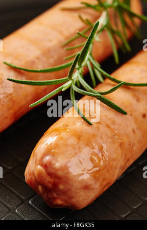 Raw sausage in pan on wooden table surrounded by ingredients - Stock Photo