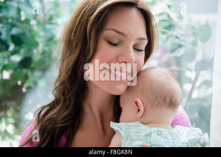 Mother holding baby daughter - Stock Photo