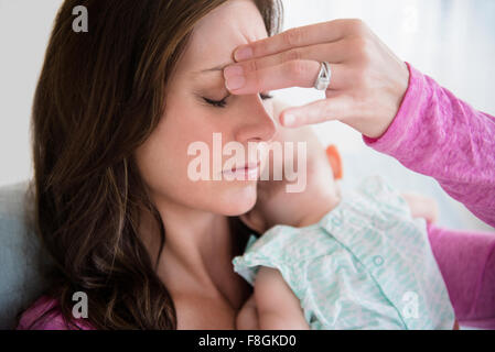 Stressed mother pinching her forehead - Stock Photo