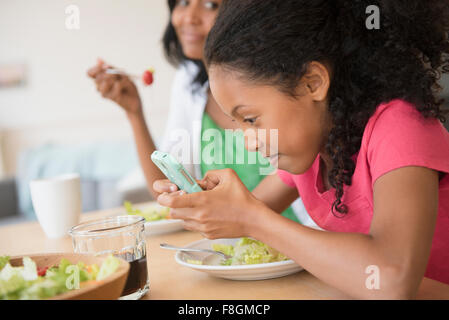 Girl using cell phone at dinner - Stock Photo