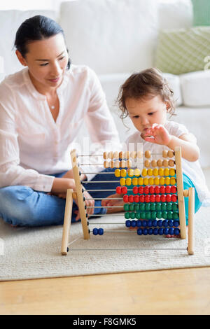 Mother and baby girl playing with abacus - Stock Photo